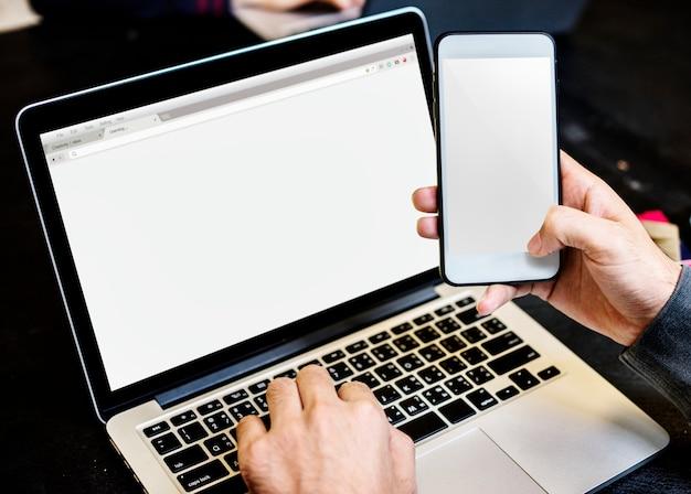 Gros plan des mains sur téléphone mobile avec fond d'ordinateur portable