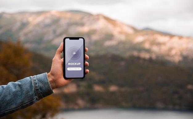 Gros plan maquette d'une main tenant un téléphone mobile sur fond de montagnes