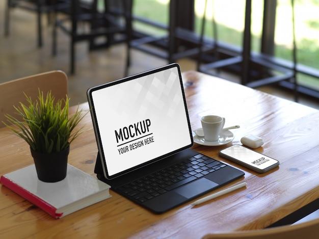Gros plan d'une table en bois avec tablette, maquette de smartphone, livre et tasse à café