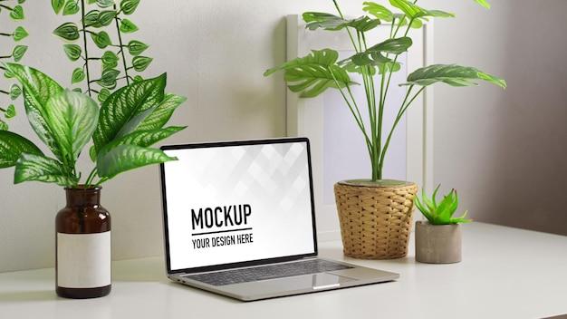 Gros plan sur la table de travail avec maquette d'ordinateur portable et maison de plantes décorée sur la table