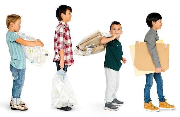 Groupe diversifié d'enfants recyclant les déchets