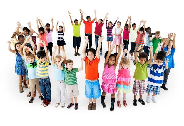 Groupe d'enfants divers debout en cercle avec les bras levés isolé sur blanc