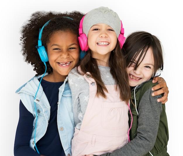 Groupe de petites filles studio souriant avec des écouteurs et des vêtements d'hiver