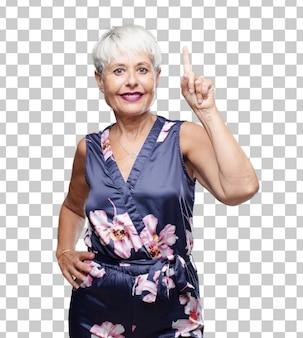 Haute femme cool souriante et à la recherche de satisfaction et de bonheur, comptant le nombre avec un doigt.