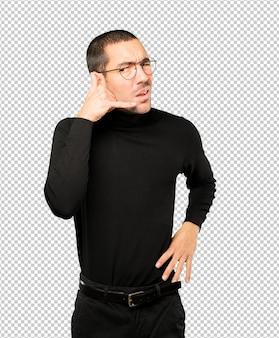Hésitant jeune homme faisant un geste d'appel avec la main
