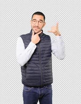 Hésitant jeune homme faisant un geste d'appeler avec la main