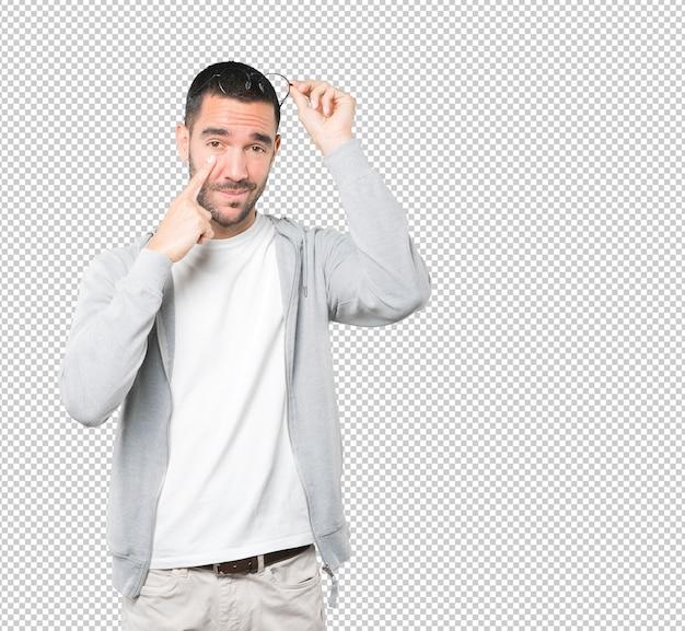Hésitant jeune homme faisant un geste de prudence avec sa main pointée vers son œil