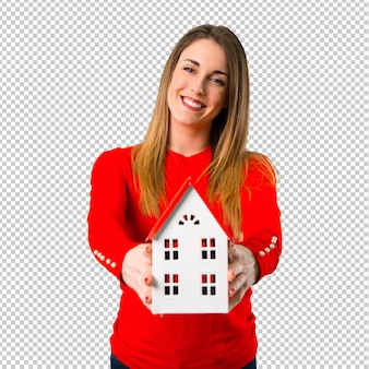 Heureuse jeune femme blonde tenant une petite maison