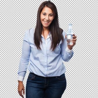 Heureuse jeune femme avec une bouteille d'eau