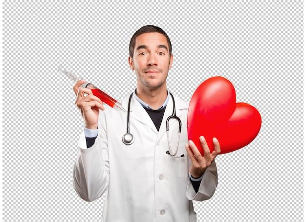 Heureux docteur tenant un coeur de jouet et une seringue sur fond blanc