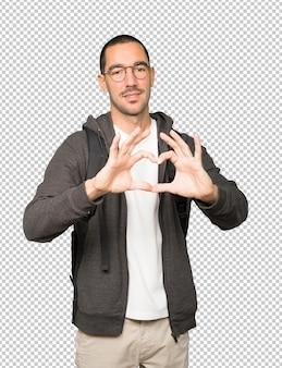 Heureux étudiant faisant un geste d'amour avec ses mains