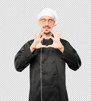 Heureux jeune chef faisant un geste d'amour avec ses mains