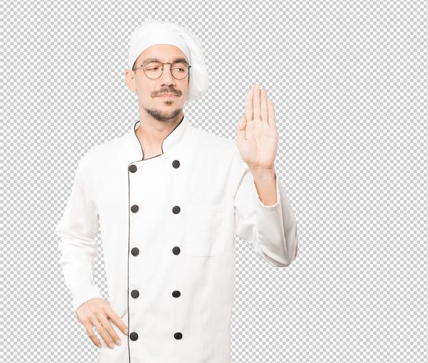 Heureux jeune chef faisant un geste d'arrêt avec sa paume
