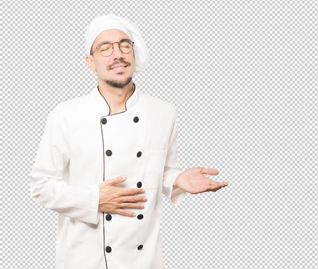 Heureux jeune chef pensant à la nourriture