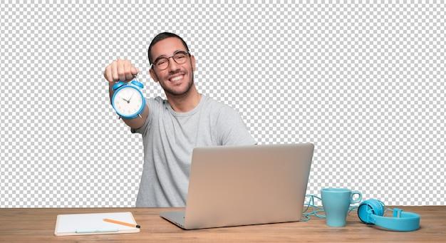 Heureux jeune homme assis à son bureau et tenant un réveil