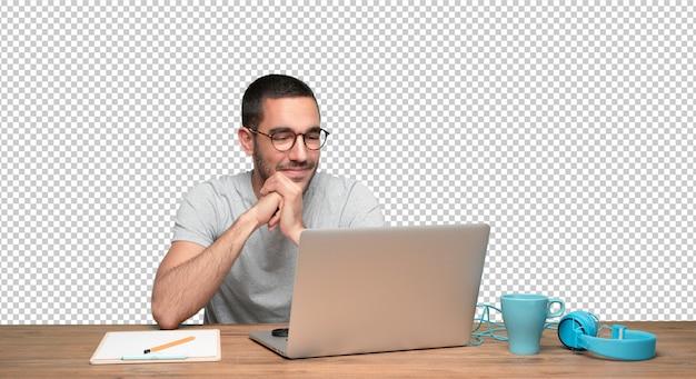 Heureux jeune homme assis à son bureau