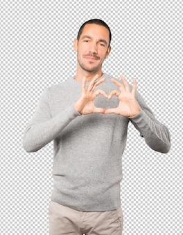 Heureux Jeune Homme Faisant Un Geste D'amour Avec Ses Mains PSD Premium