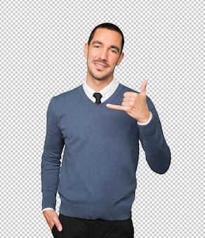 Heureux jeune homme faisant un geste d'appel avec la main