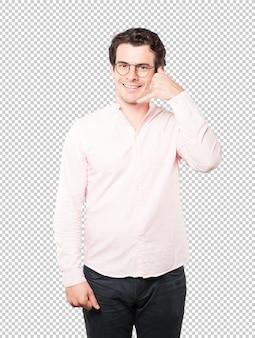 Heureux jeune homme faisant un geste d'appeler avec la main