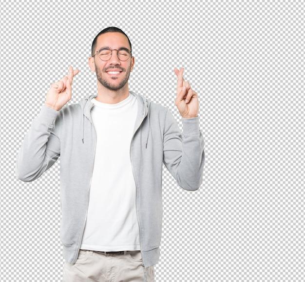 Heureux jeune homme faisant un geste de doigts croisés