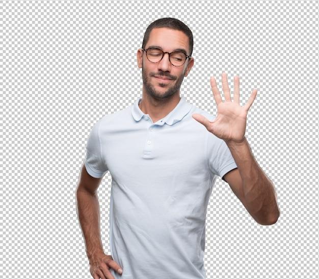 Heureux jeune homme faisant un geste du numéro cinq
