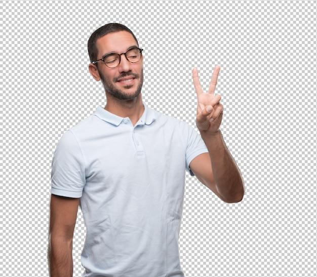 Heureux jeune homme faisant un geste du numéro deux
