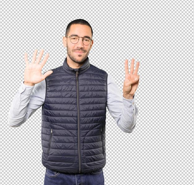Heureux jeune homme faisant un numéro huit avec ses mains