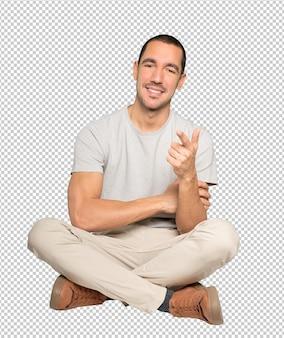 Heureux jeune homme pointant vers vous avec son doigt
