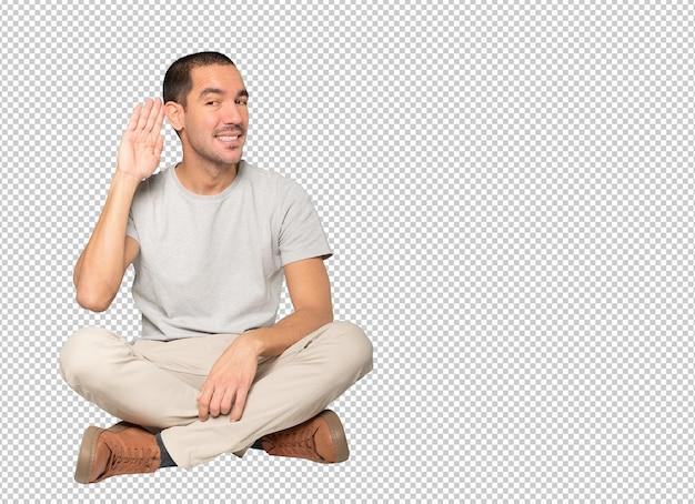 Heureux jeune homme souriant et faisant un geste d'essayer d'entendre quelque chose