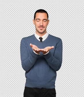 Heureux jeune homme tenant quelque chose avec sa main