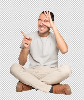 Heureux jeune homme utilisant ses mains comme des jumelles