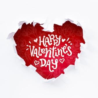Heureux lettrage de la saint-valentin dans un trou en forme de coeur rouge