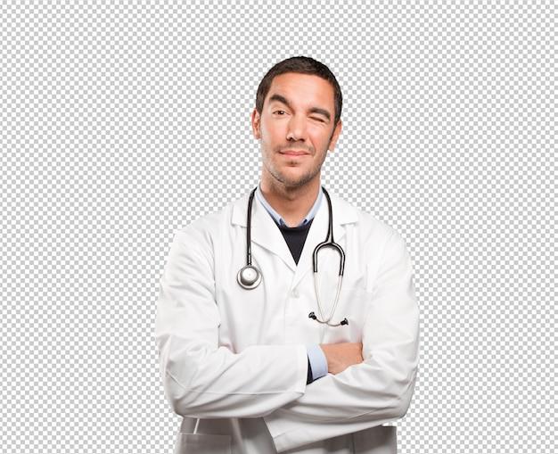 Heureux médecin clignant de l'oeil sur fond blanc