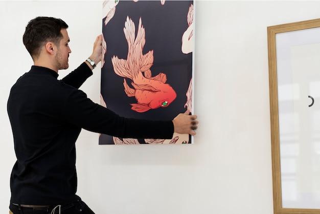 Un homme accroché un cadre photo sur le mur