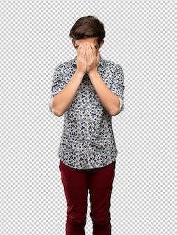 Homme adolescent avec une chemise à fleurs et des lunettes avec une expression fatiguée et malade