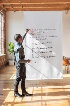 Homme d'affaires écrit sur une affiche blanche
