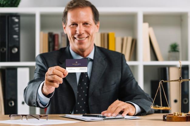 Homme d'affaires élégant présentant une carte de visite mocku