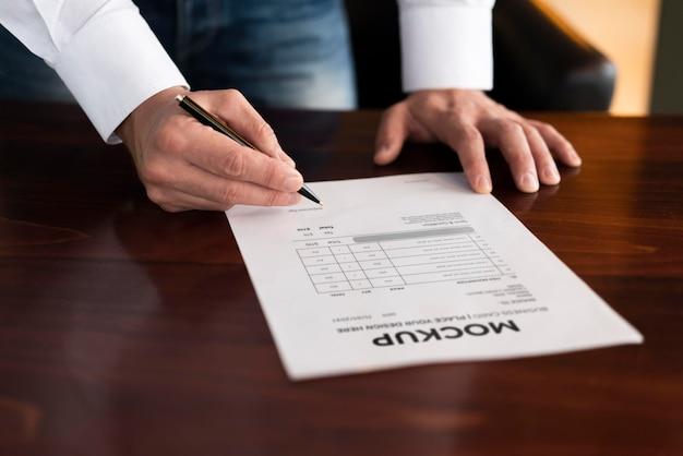 Homme d'affaires grand angle écrit sur maquette de papier