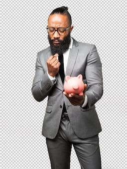 Homme d'affaires noir épargnant avec une tirelire