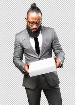 Homme d'affaires noir tenant une boîte blanche