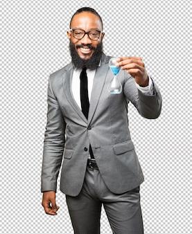 Homme d'affaires noir tenant un sablier