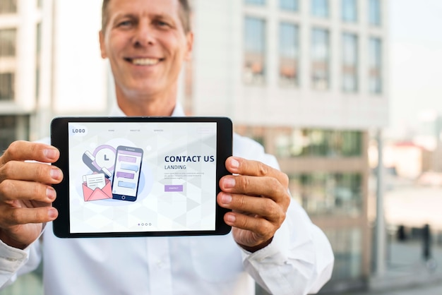 Homme d'affaires de smiley à l'extérieur tenant une tablette numérique horizontale