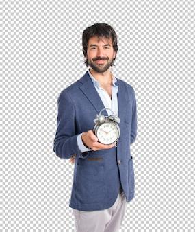 Homme d'affaires tenant une horloge sur fond blanc