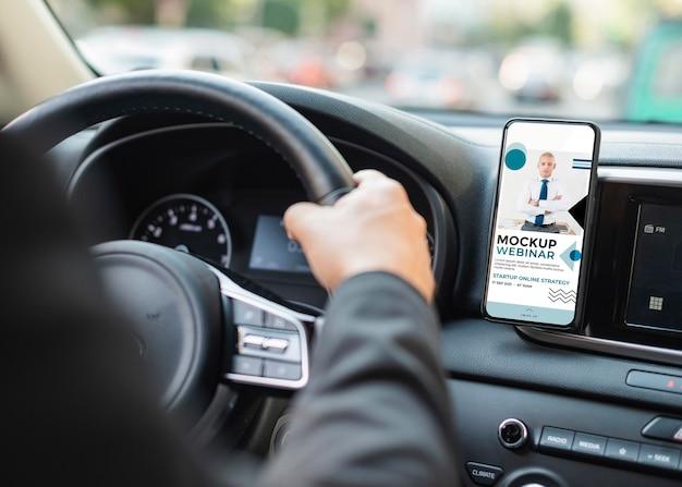 Homme d'affaires en voiture avec maquette de téléphone