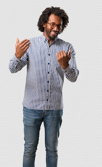 Homme afro-américain de belles affaires invitant à venir, confiant et souriant, faisant un geste de la main, étant positif et amical