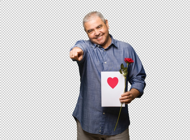 Homme âgé moyen célébrant la saint valentin gaie et souriant