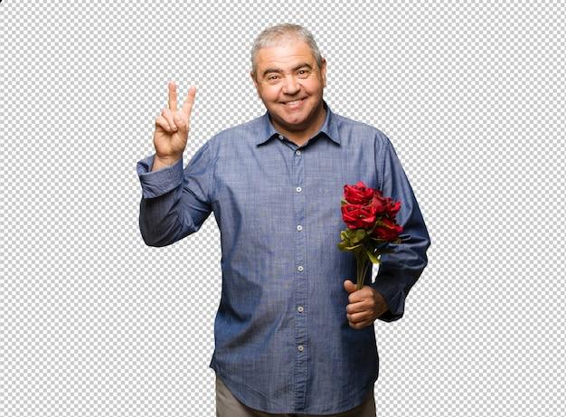 Homme d'âge moyen célébrant la saint-valentin en s'amusant et heureux de faire un geste de victoire