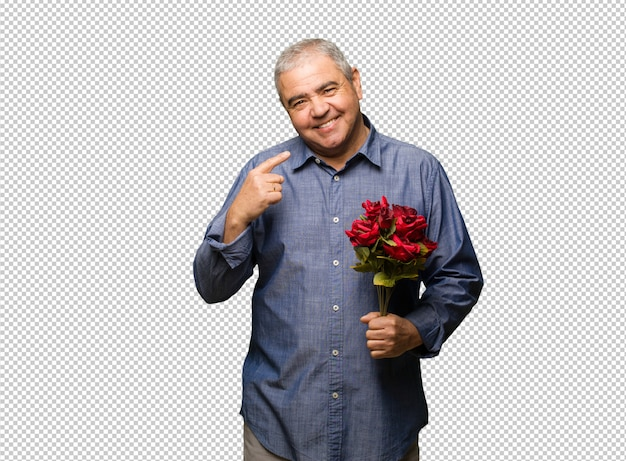 Homme âgé moyen célébrant saint valentin sourit, pointant la bouche