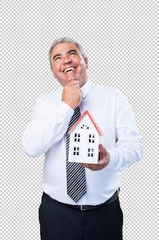 Homme d'âge mûr pensant tenir une maison