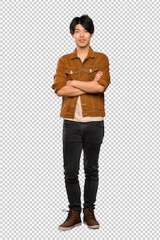 Homme asiatique avec une veste marron en gardant les bras croisés en position frontale